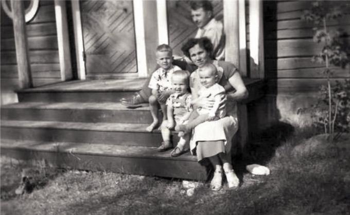 Mustavalkoinen kuva, jossa kolme lasta, mies ja nainen istuvat portailla.